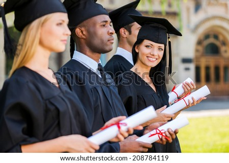 Happy graduate. Four college graduates standing in a row and holding their diplomas while one woman looking at camera and smiling  - stock photo