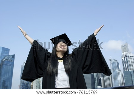 Happy graduate girl with outstretched arms in city