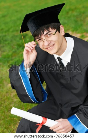 Happy graduate student in gown with diploma over green grass