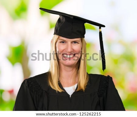Happy Graduate Woman Holding Books against a nature background
