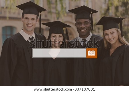 Happy graduation. Four college graduates in graduation gowns standing close to each other and smiling - stock photo