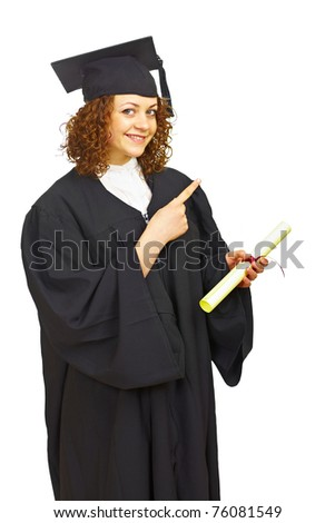 Happy graduation girl with diploma pointing right isolated over white background - stock photo