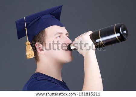 happy graduation man drinking champagne over grey background - stock photo