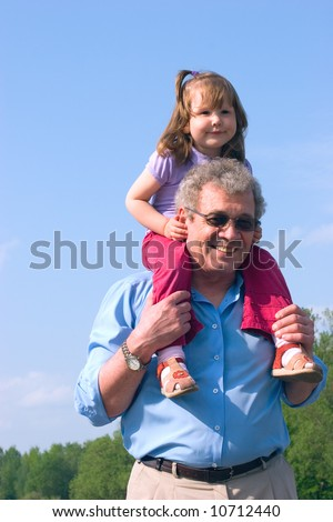 Happy granddad with granddaughter on his shoulders over skies and forest background - stock photo