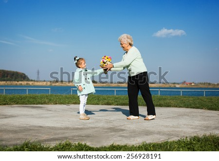 happy granddaughter giving flowers to grandmother outdoors - stock photo
