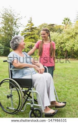 Happy granddaughter talking with grandmother in her wheelchair in the park on sunny day - stock photo
