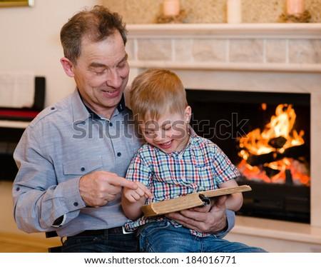 Happy grandfather and grandchild reading a book - stock photo