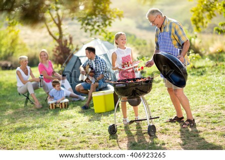 happy grandfather and granddaughter making barbecue for family - stock photo