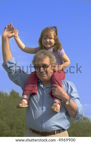 Happy grandfather and granddaughter outside over vivid blue sky