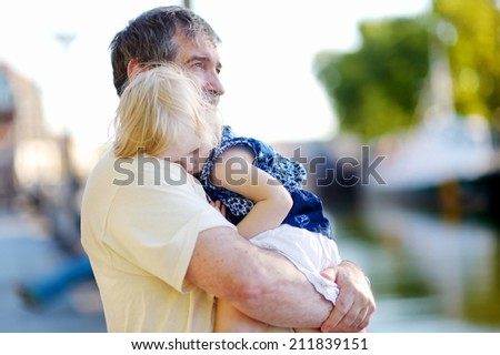 Happy grandfather holding his adorable little sleeping grandchild on nice summer day - stock photo