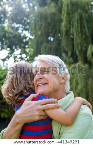 Happy grandfather hugging grandson at back yard - stock photo