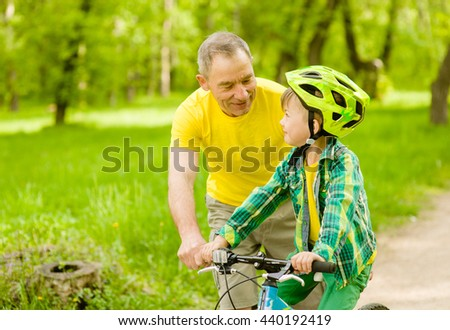 Happy grandfather teaches his grandson to ride a bike - stock photo