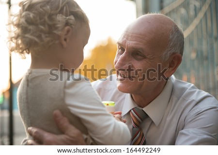 Happy grandfather with cute curly granddaughter - stock photo