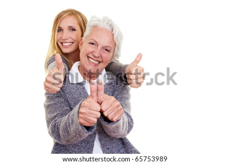 Happy grandma and her granddaughter holding their thumbs up - stock photo