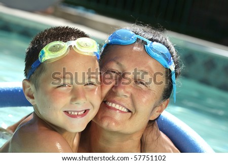 Happy grandma and her grandson in a sparkling pool - stock photo