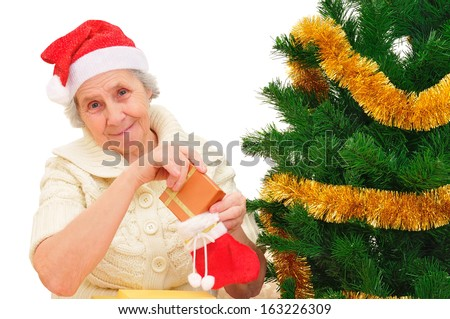 happy grandma in Santa cap decorating Christmas gifts on white background - stock photo