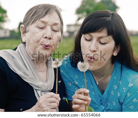 Happy grandmother and grand daughter with dandelions on the meadow - stock photo