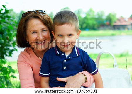 happy grandmother and grandchild embracing outside - stock photo