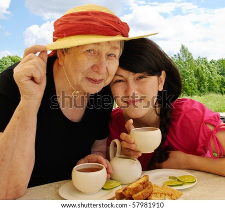 Happy grandmother and granddaughter drinking tea - stock photo