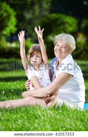 Happy grandmother and granddaughter in the park - stock photo