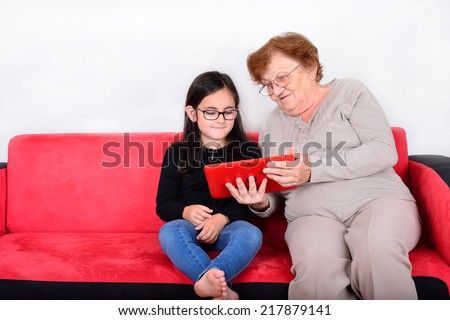 Happy grandmother and granddaughter using Tablet PC - stock photo