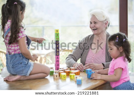 Happy grandmother and granddaughters playing with alphabet blocks at table - stock photo
