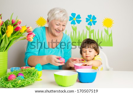 Happy grandmother and grandson color eggs for Easter at home.  - stock photo