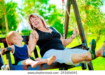 Happy grandmother and grandson on a swing - stock photo