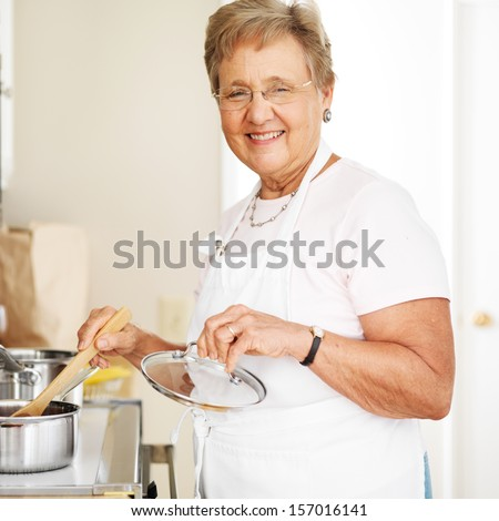happy grandmother cooking in kitchen - stock photo