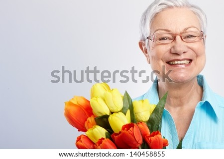 Happy grandmother holding bouquet of tulips at mother's day, smiling. - stock photo