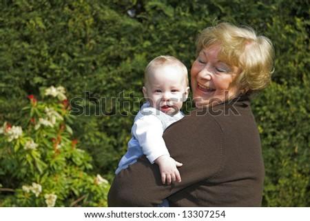 Happy grandmother holding grandson in garden - stock photo
