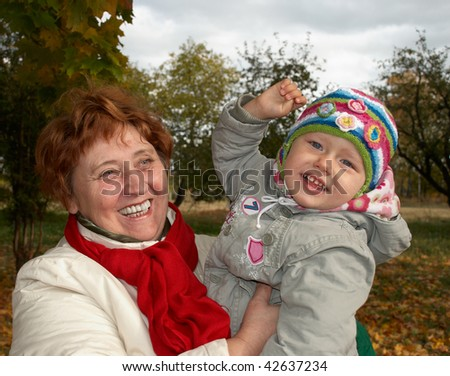 Happy grandmother holding her granddaughter in her arms - stock photo