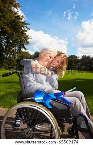 Happy grandmother in wheelchair with her grandchild in a park - stock photo