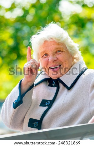 happy grandmother is resting on a park bench