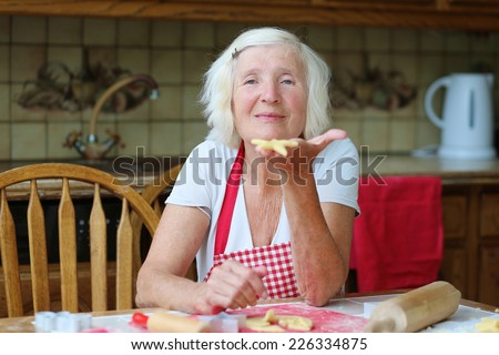 Happy grandmother, loving caring senior woman, wearing red apron, baking tasty sweet cookies for her grandchildren sitting at the table in classic traditional wooden kitchen - stock photo