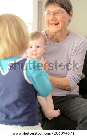 Happy grandmother play with her grandchildren at home. Concept photo of newborn, baby, grandmother, grand motherhood, senior,retirement, lifestyle - stock photo
