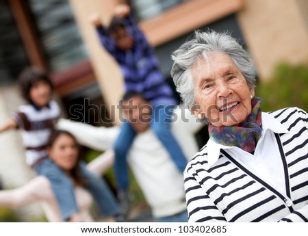 Happy grandmother smiling with her family at the background - stock photo