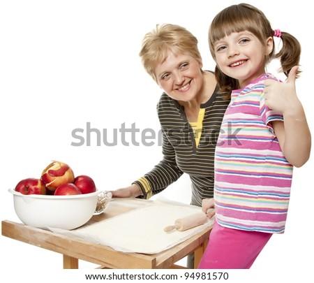 happy grandmother teaching her granddaughter bake apple pie, white background - stock photo