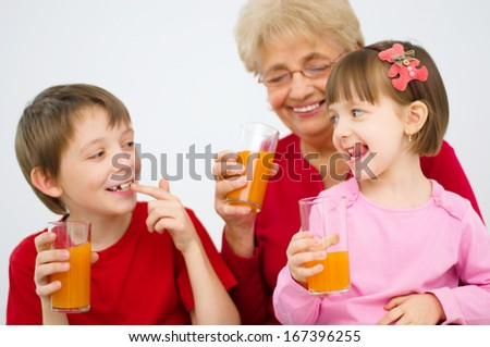 happy grandmother with grandchildren drinking fruit juice at home - stock photo