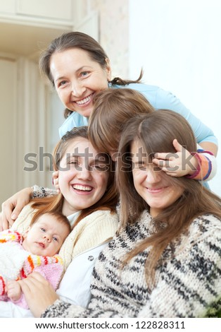 Happy grandmother with her daughters and granddaughters in home - stock photo