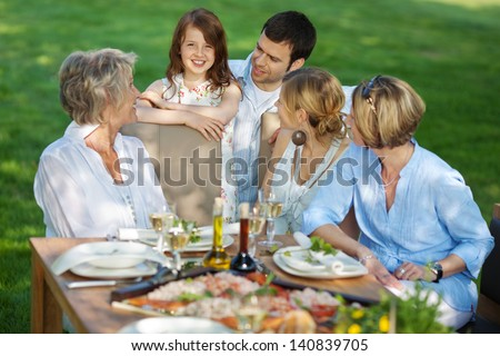 happy grandmother with her family sitting outdoors - stock photo