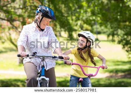 Happy grandmother with her granddaughter on their bike on a sunny day