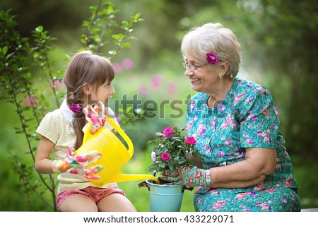 Happy Grandmother with her granddaughter working in the garden - stock photo