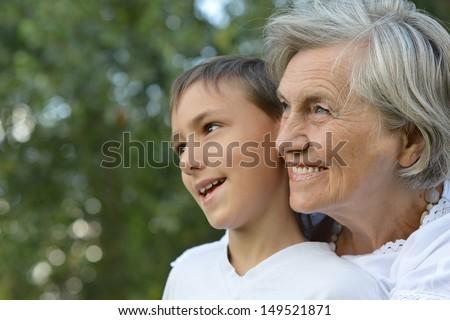 happy grandmother with her grandson for a walk in a summer park - stock photo