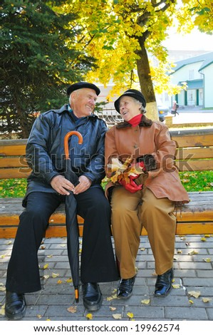 happy grandparent on bench in park - stock photo