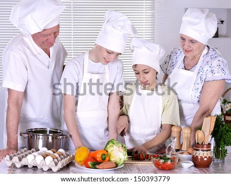 Happy grandparents and their grandchildren cook together - stock photo
