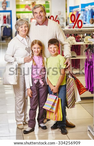 Happy grandparents and their grandchildren standing in one of departments of mall - stock photo