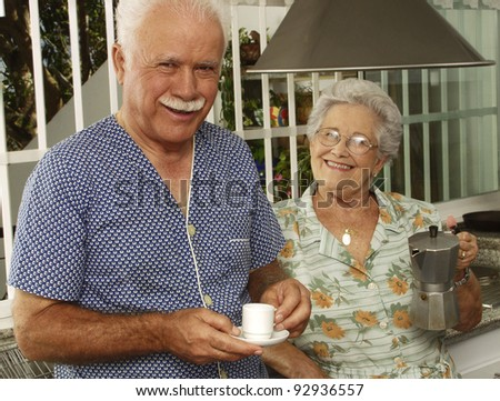 Happy grandparents couple drinking coffee in the kitchen. - stock photo