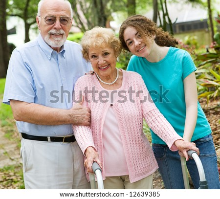Happy grandparents enjoying time with their teen granddaughter. - stock photo