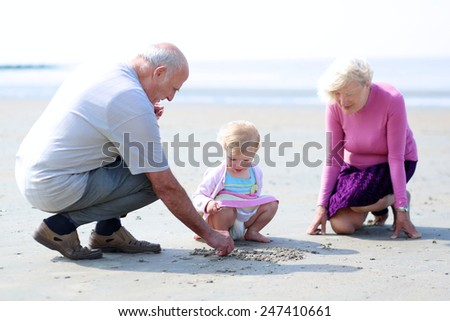 Happy grandparents playing with their granddaughter, cute toddler girl, at the beach building castles and drawing on the sand - active retirement concept. Selective focus on child - stock photo